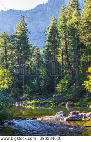 Charming Yosemite Valley. Forest stream. The shady forest is reflected in the water. Yosemite Park is located on the slopes of the Sierra Nevada