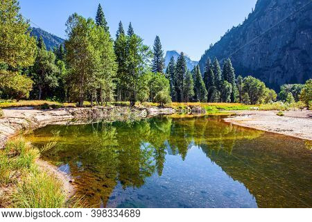 Charming little lake in the Yosemite Valley. Yosemite Park is located on the slopes of the Sierra Nevada. The El Capitan and trees is reflected in the smooth water