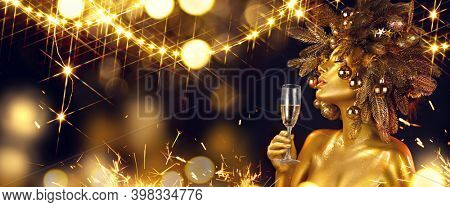 Golden Christmas Woman with champagne. Beautiful girl drinking sparkling wine, over glowing holiday background. Xmas, New Year celebration