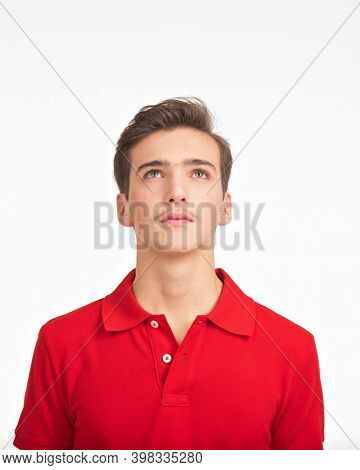 Photo of  young  confident man looking up. Portrait of handsome guy with a calm emotions looking up.  Teenager  lifts a head up.