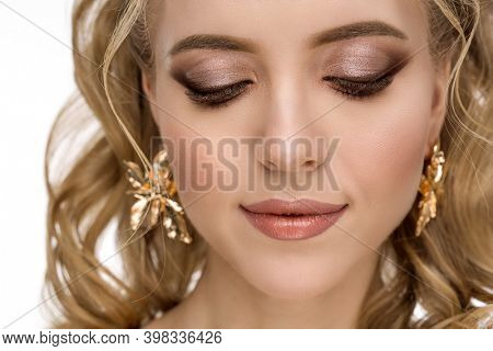 Beautiful fashion girl with hair coloring in blond. Perfect beauty woman, long blonde healthy curly hair, wavy hairstyle in beauty salon. Famale with perfect fresh skin and makeup. Face closeup