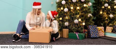 Merry Christmas And Happy Holidays. Cheerful Mom And Her Cute Daughter Girl Opening A Christmas Pres
