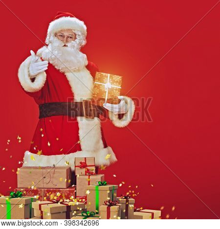 Portrait of the good old Santa Claus carrying gifts on Christmas on a red background. Delivery service of Santa Claus.