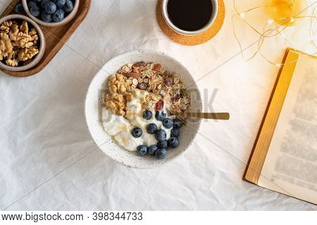 Top View Book And Christmas Healthy Lifestyle Breakfast With Granola Muesli And Yogurt In Bowl On Wh