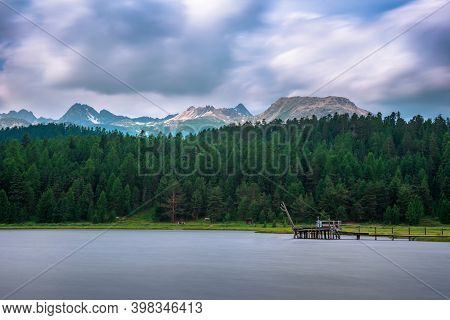 Footbridge Over The Lake Of Staz Near St. Moritz In Switzerland With Swiss Alps In The Background. T