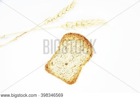Crusty Bread Toast Slice Next To Two Ears Of Wheat On White Background. Healthy Food Concept