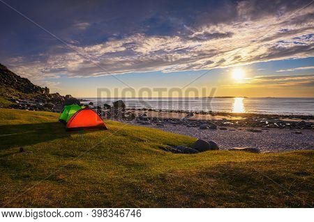 Camping With Tents On Uttakleiv Beach In Lofoten Islands, Norway, During Sunset.