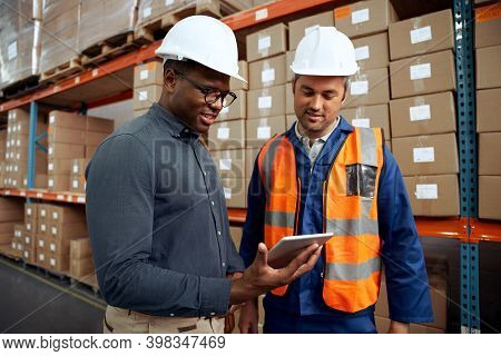 Multi Ethnic Factory Engineers Checking Digital Tablet At Factory Warehouse