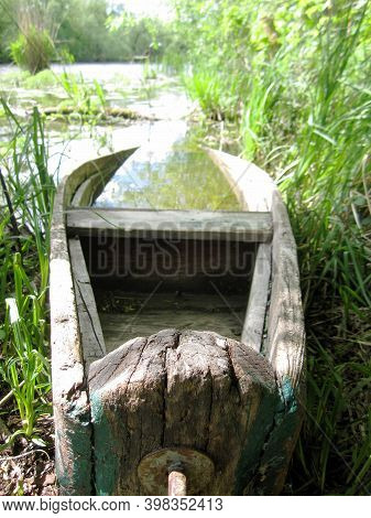 Old Wooden Broken Boat For Swimming On Banks Water In Natural Reeds. Photography Consisting Of Old W