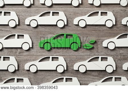 Top view of green electric car between polluting fossil combustion vehicles. Wooden cut out of single pollution free electric car. Eco friendly, clear ecology driving, no pollution and emission free.