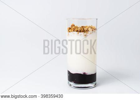 Healthy Layered Dessert With Bio Yogurt, Granola And Balck Currant Jam On White Background.