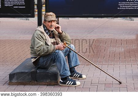 Frustrated  Sad Elderly Man With Stick Sitting On Street In Solitude And Looking At Camera. Poverty