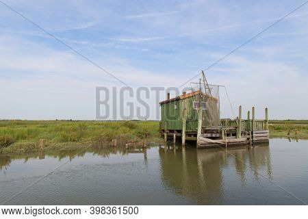 Green cabin at wooden boat dock in landscape at French Charente