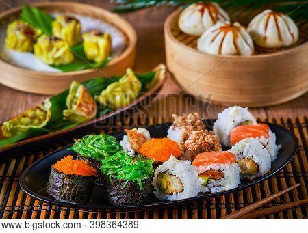 Sushi Set Uramaki, Gunkan, Gyozas Dumplings And Wakame Salad In Ceramic Plates With Soy Sauce And Ch