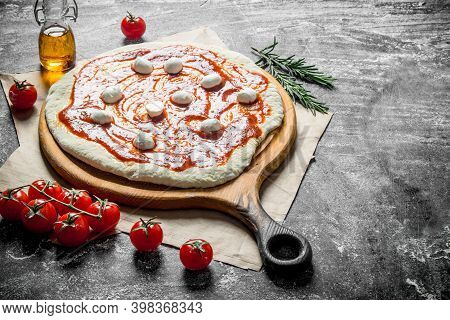 Preparation Pizza. Dough With Tomato Paste And Mozzarella. On Rustic Background