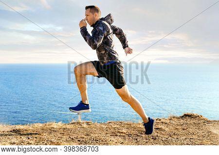 Male Runner In Windbreaker Running In Background Sky And Sea