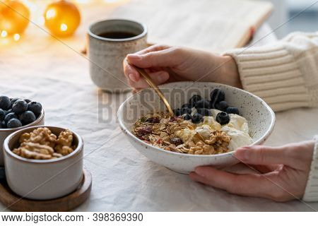 Reading Book And Eating Healthy Christmas Holiday Winter Breakfast With Granola Muesli And Yogurt In