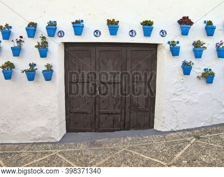 Blue Flowerpots Around A Wooden Door In An Andalusian Old Town. Spain