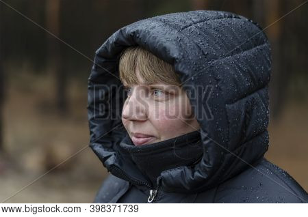 Portrait Of A Middle-aged Woman In Black Hooded Jacket In  Autumn Rain. Woman Of 40-45 Years Old Loo