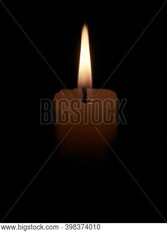 Burning Candle Isolated On Black Background. Candlelight On Black Background