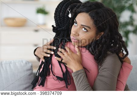 Irritated Black Lady Hugging Her Girlfriend With Annoyed Face Expression, Fake Friendship Concept. T