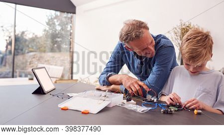 Grandson With Grandfather Assembling Electronic Components To Build Robot Together At Home
