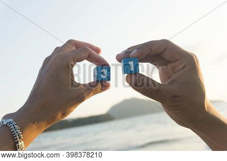 Man And Women Holds A Number Thirty One In Hands, Sunset, Sea Background.