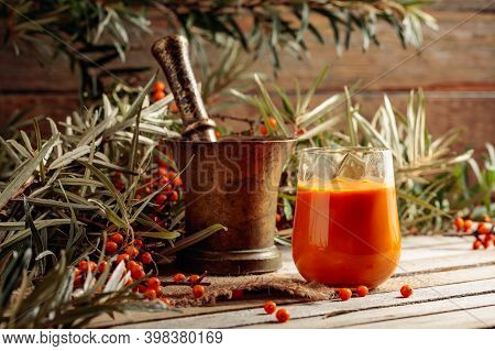 A Glass Of Sea Buckthorn Juice With Fresh Berries On An Old Wooden Table. A Healthy Vitamin Drink.