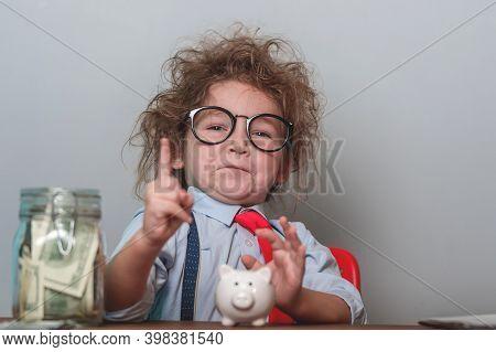 Funny Little Kid Investor With Finger Poiting Up And Biggy Bak, Calculator And Jar With Money. Child