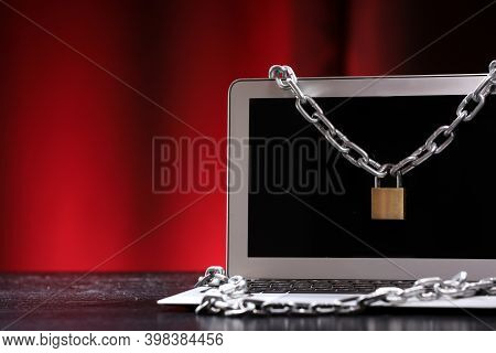 Laptop Tied With An Iron Chain With A Lock On A Dark Office Table Against Black And Red Background.