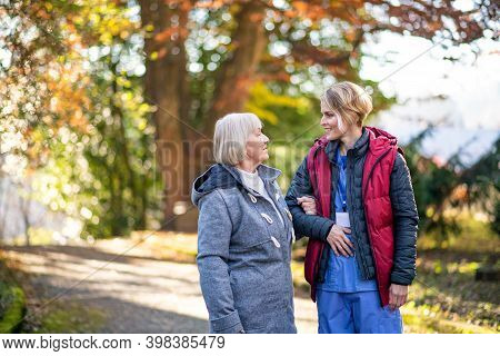 Senior Woman With Caregiver Outdoors On A Walk In Park, Coronavirus Concept.