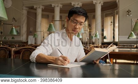 Attractive Asian Student With Textbook Thoughtfully Making Study Notes In Library. Young Confident G