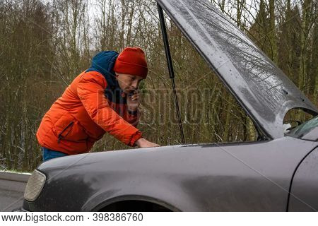 Man In A Winter Orange Jacket And Hat Is Talking On The Phone And Looking Under The Hood Under The C