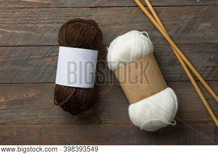 White And Brown Skeins Of Hand Spun Yarn With Blank Kraft Paper Wrap Labels For Mockup On Rustic Woo