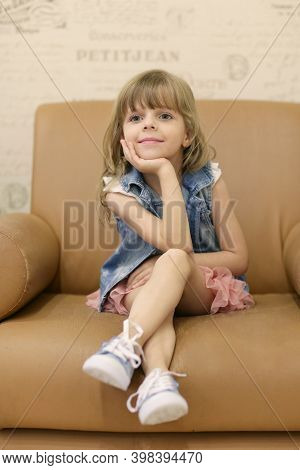 Little Blond Baby Girl Sit On Armchair Smiling Close Up Portrait On Retro Interior Background
