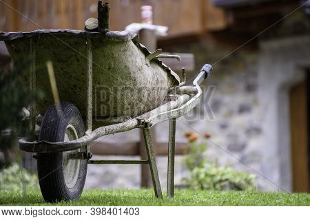 Old Iron Wheelbarrow. Decorative Vintage Object In The Garden Of A House.