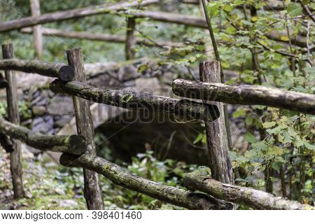 Old Arch Bridge Over A Mountain Stream. Mountain Path With Wooden Fence.