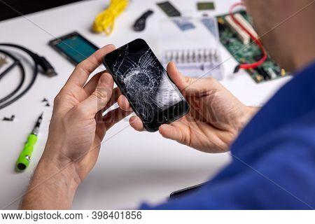 Smartphone With Broken Cracked Screen In Technician Hands. Phone Repair Service