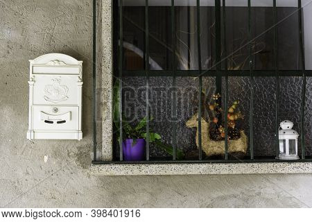 Christmas Decorations On A Window. Detail Of White Lamp And Deer With Berries. Old Mailbox Painted W
