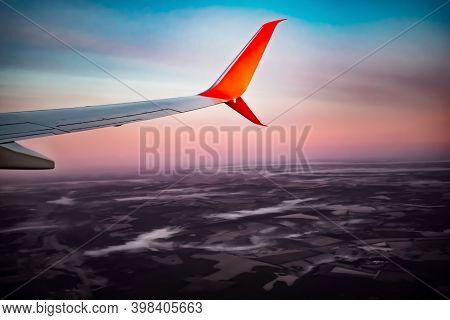 The Wing Of An Airplane Flying Above The Clouds Over Dark Brown Ground At Dawn. White-orange Plane F