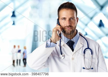 Confident Male Doctor Talking With His Patient On Mobile Phone While Standing On The Hospital Foyer