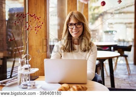 Confident Mature Woman Sitting In The Cafe And Using Her Laptop