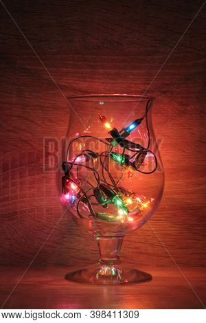 Glass goblets and bottles with christmas electric garlands on dark background