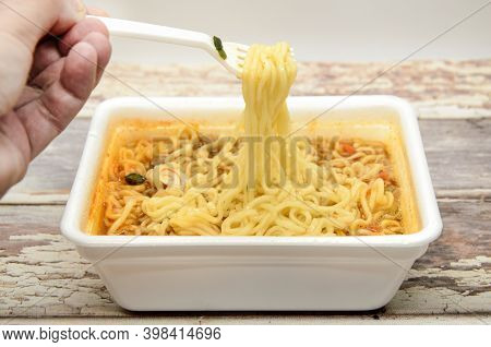 Instant Noodles With Dry Vegetables And Spices With Red Pepper In Disposable Container With Plastic