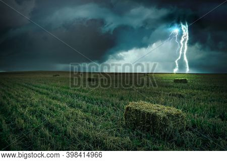 Beautiful Thunderstorm Over Green Field. Lightning Striking From Dark Cloudy Sky