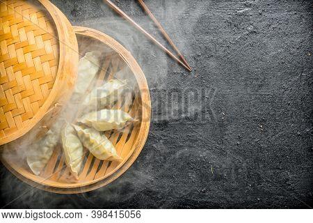Hot Gedza Dumplings In A Bamboo Steamer. On Black Rustic Background