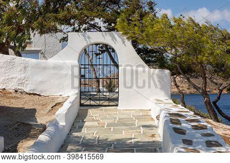 Cast Iron Gate In A White Wall. Entry To The Agia Irini, Saint Irene, Greek Orthodox Church. A Stone