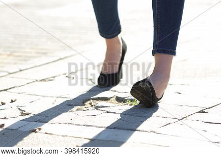 Close Up Of A Woman Legs With High Heels Spraining Ankle While Walking In The Street