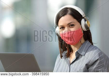 Woman Wearing Protective Mask To Avoid Coronavirus Contagion Or Pollution Using Laptop And Headphone