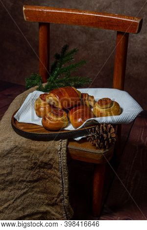Homemade Buns On A White Towel. Buns And Decorations On A Wooden Tray. Next To The Buns Are Cones An